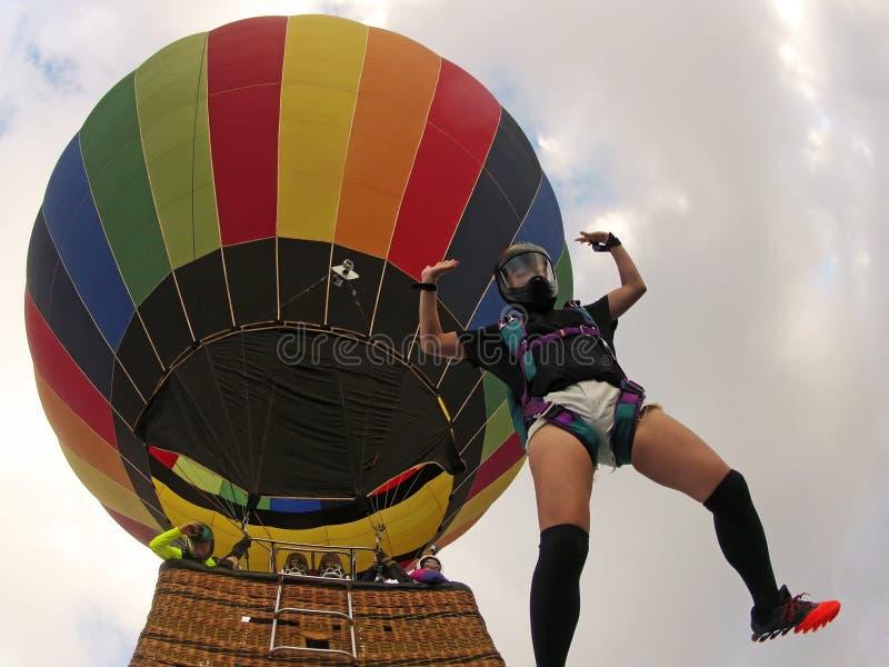 Frau springt von einem Heißluftballon an einem Sommertag lizenzfreies stockfoto