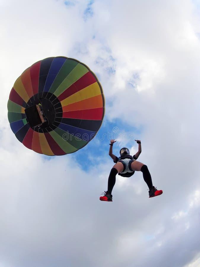 Frau springt von einem Heißluftballon an einem Sommertag lizenzfreie stockbilder
