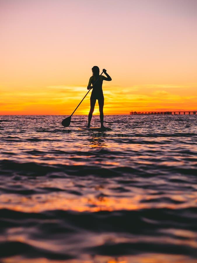 Frau stehen oben Paddeleinstieg an der Dämmerung auf einem flachen warmen ruhigen Meer mit schönen Sonnenuntergangfarben stockbild