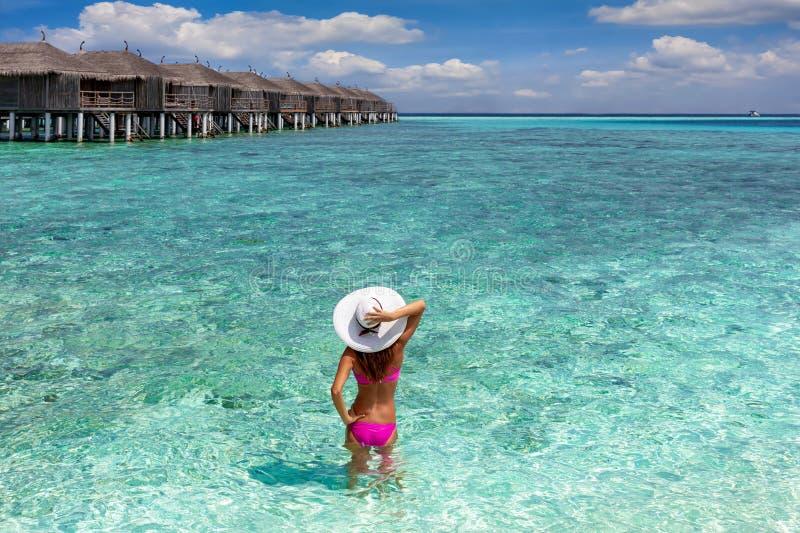 Frau steht im Türkiswasser der Malediven stockfoto