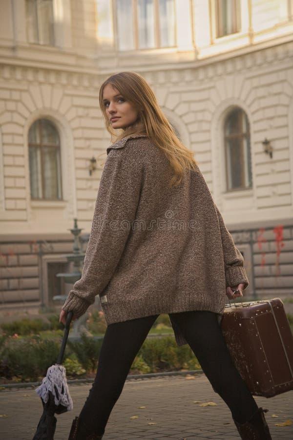 Frau steht mit Koffer vor Hotel lizenzfreies stockfoto