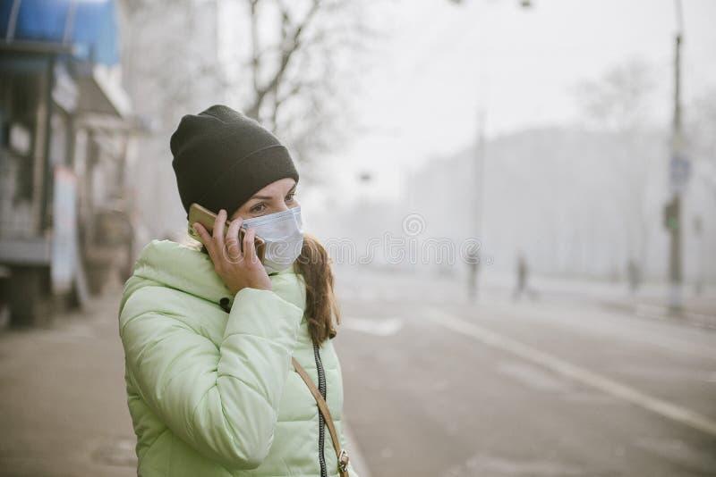 Frau steht nahe einer Straße in der Stadt in einer schützenden medizinischen Maske Schutz vor Viren in der Stadt lizenzfreie stockfotos