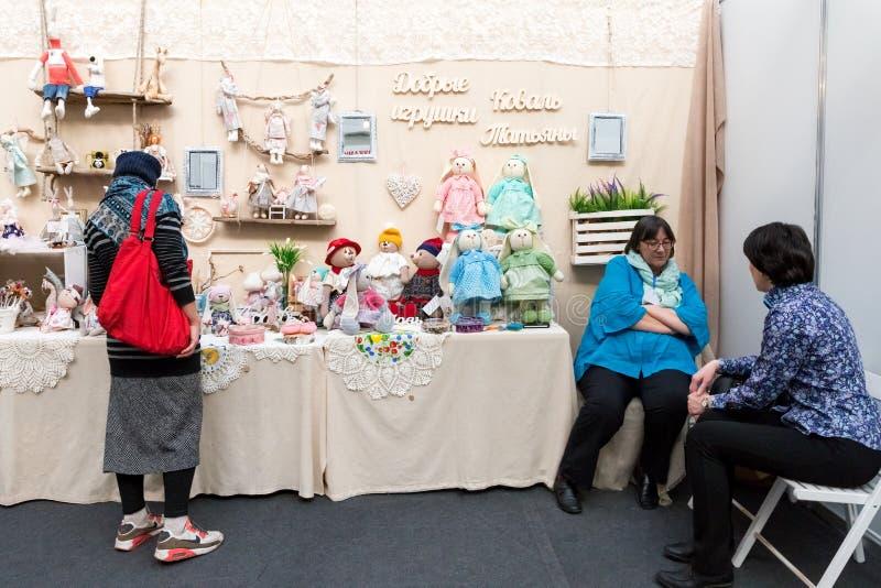 Frau steht am Stand mit Spielwaren nahe bei sitzendem Needlewoman Tatyana Koval lizenzfreies stockbild