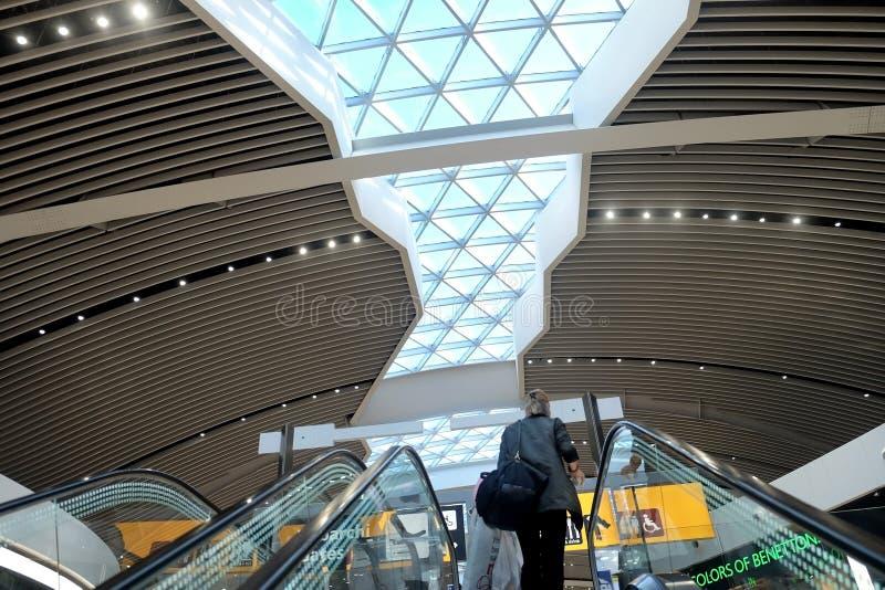 Frau steigt auf die Rolltreppe im Flughafen Fiumicino stockfoto