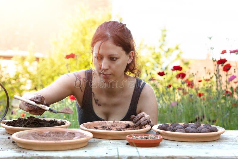 Frau stellt Samenbälle oder Samenbomben auf einem Holztisch her lizenzfreie stockfotografie