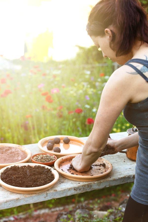 Frau stellt Samenbälle oder Samenbomben auf einem Holztisch her stockfoto
