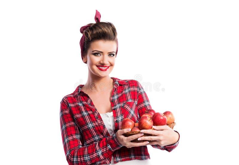 Frau, Stift-obenfrisur, die Korb mit Äpfeln hält Herbst harve lizenzfreies stockbild