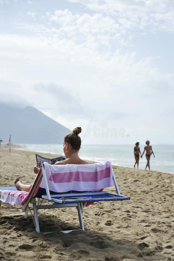 Frau am Strand entspannt sich, indem sie ein Klatschmagazin liest Auf dem Hintergrund geht ein paar Liebhaber stockfoto