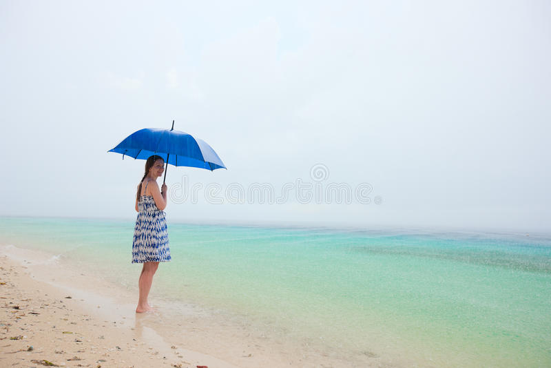Frau am Strand unter Regen lizenzfreie stockbilder