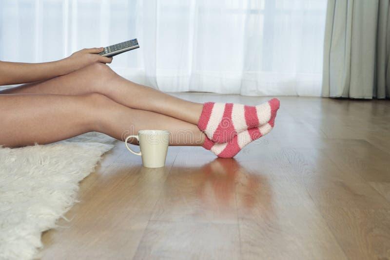 Frau in Stripey-Socken mit Fernbedienung lizenzfreies stockfoto