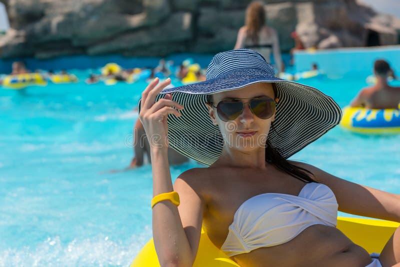 Frau in Sun-Hut, der in Pool-inneres Rohr schwimmt lizenzfreie stockfotos