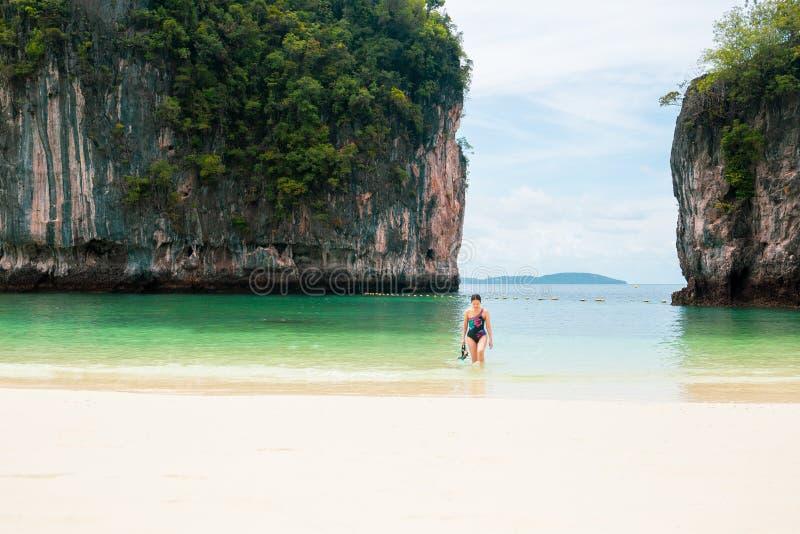 Frau in swimmimg Klage, die das Schnorcheln der Maske gehend auf tropischen Strand hält stockfotos