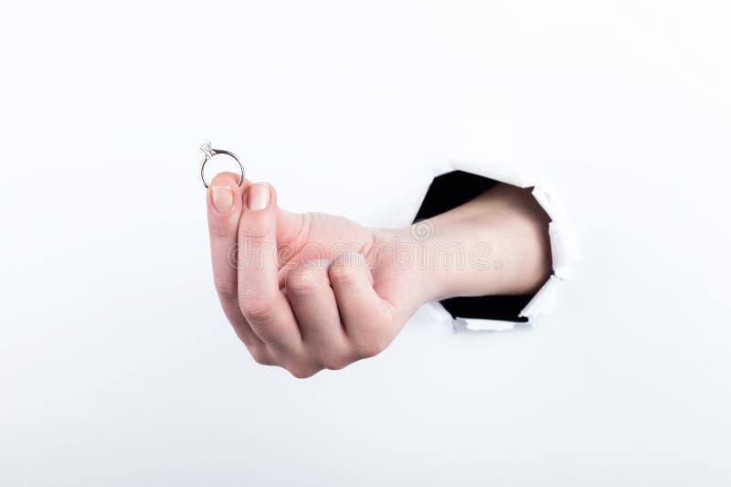 Frau teilen von einem Loch im Papier, hält einen Ehering, macht eine Verpflichtung aus Isolat auf weißem Hintergrund lizenzfreies stockfoto