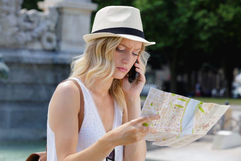 Frau am Telefon, das AR-Karte schaut stockbild