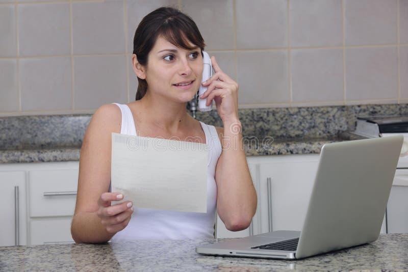 Frau am Telefon mit Rechnung lizenzfreie stockbilder