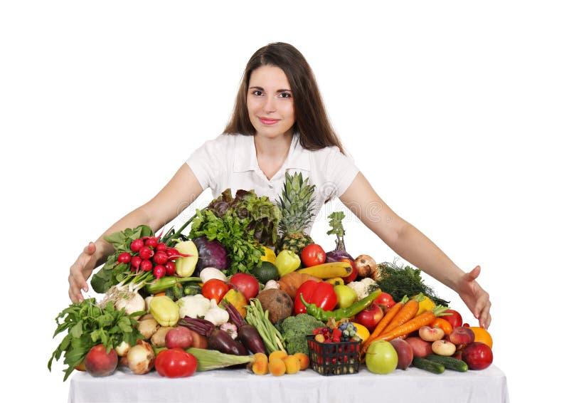 Frau am Tisch mit Obst und Gemüse lizenzfreie stockfotografie
