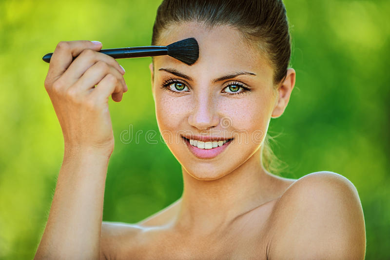 Frau tont vom Pinsel auf Ihrem stockbilder