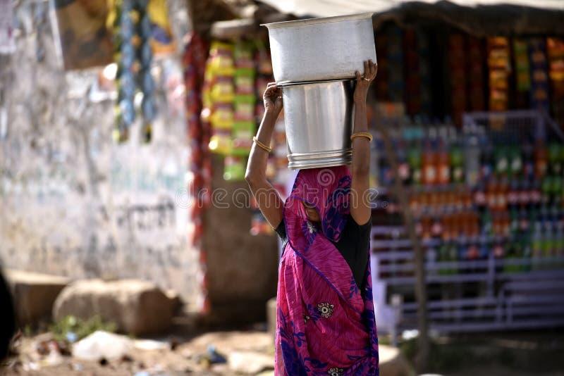 Frau trägt Eimer Wasser lizenzfreie stockfotos