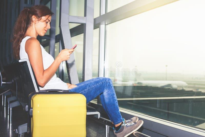 Frau trägt Ihr Gepäck am Flughafenabfertigungsgebäude lizenzfreies stockbild