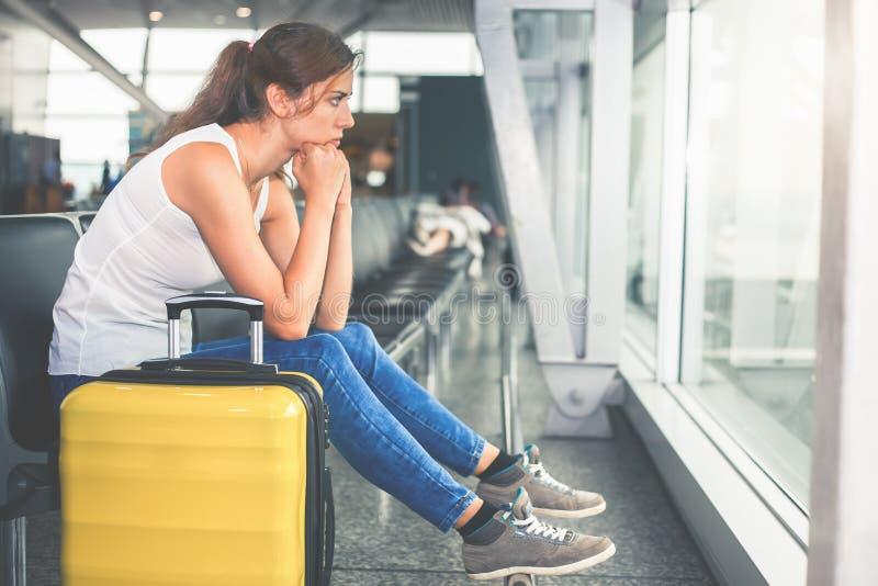 Frau trägt Ihr Gepäck am Flughafenabfertigungsgebäude lizenzfreies stockfoto