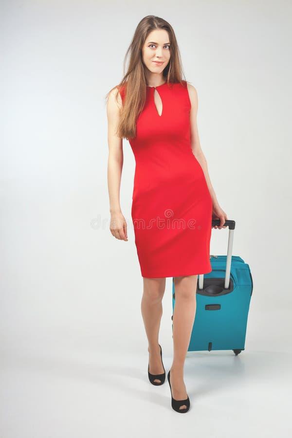 Frau trägt Ihr Gepäck am Flughafenabfertigungsgebäude stockfotografie