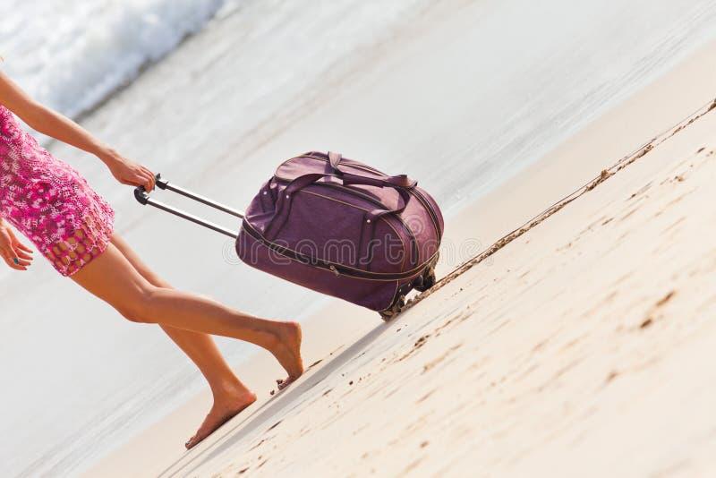 Frau trägt Ihr Gepäck am sandigen Strand lizenzfreies stockbild