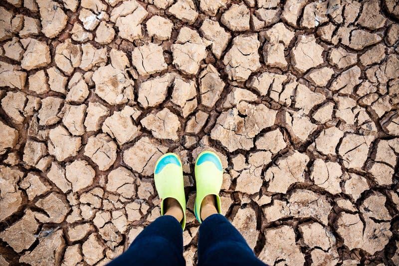 Frau tragen die Gummischuhe, die auf Dürre stehen stockfoto