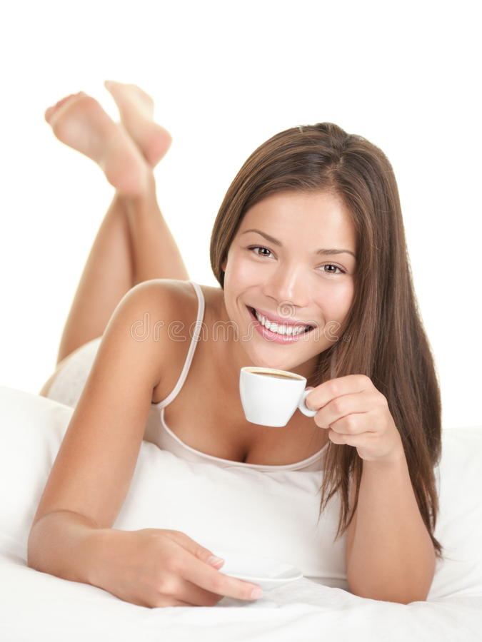 Frau in trinkendem Kaffee des Betts lizenzfreies stockbild