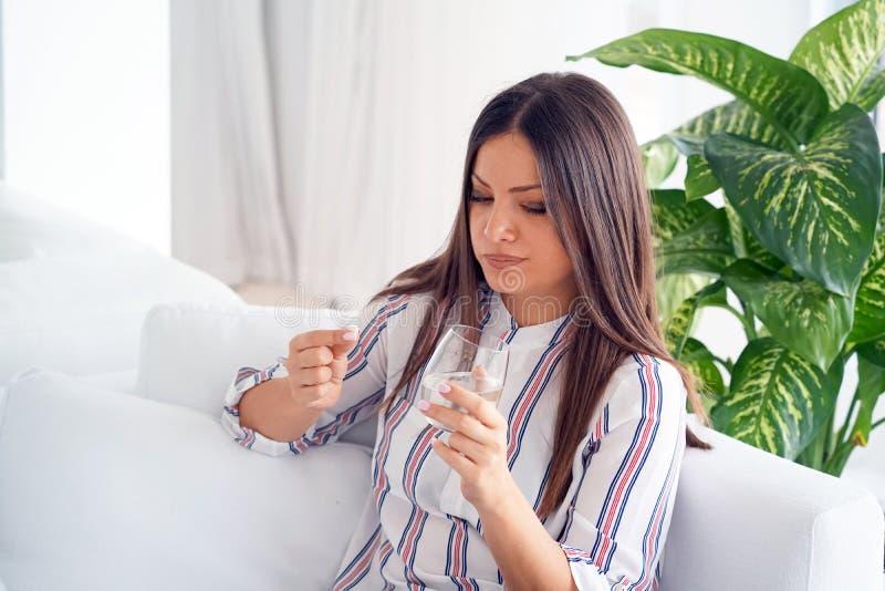 Frau trinkt eine Pille von den Schmerz stockbild