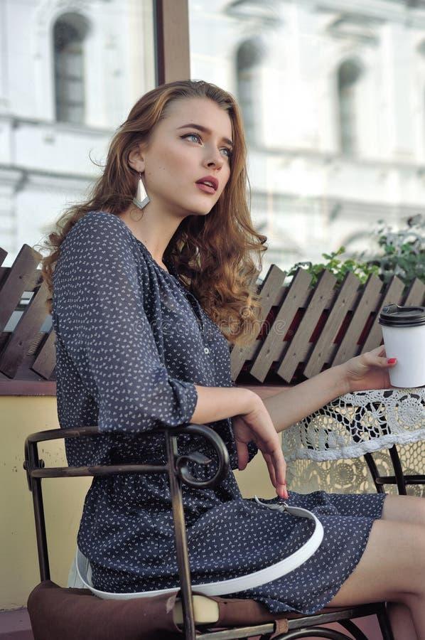 Frau trinkt Kaffee in einem Café im Freien lizenzfreie stockfotografie