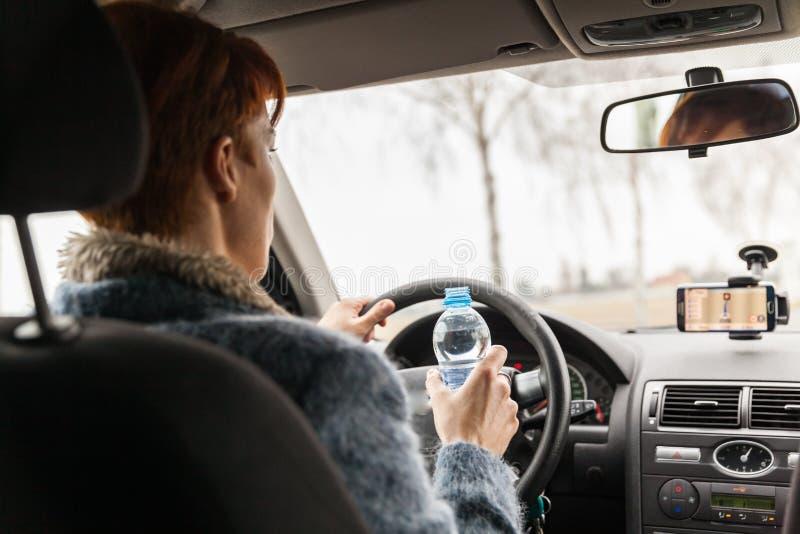 Frau trinkt Wasserweileautofahren stockbild