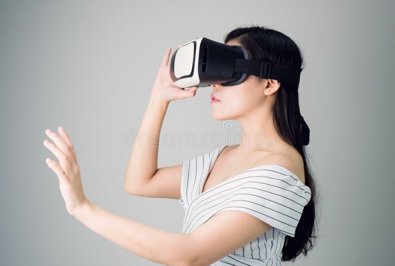 Frau trug einen Kopfhörer der virtuellen Realität, der simuliert, die Wirklichkeit und schaute oben, um zu sehen, was die virtuel lizenzfreie stockbilder