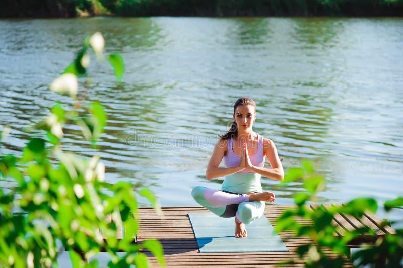 Frau tun Yoga das im Freien Frauentrainieren wesentlich und Meditation für Eignungslebensstilverein am Naturhintergrund lizenzfreie stockfotografie