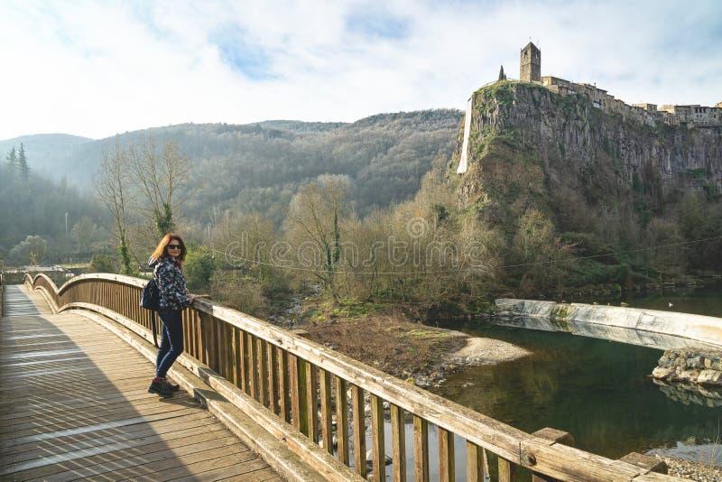 Frau turist wirft auf der alten Holzbrücke gegenüber von eindrucksvollem Klippendorf Castellfullit de la Roca auf lizenzfreies stockfoto