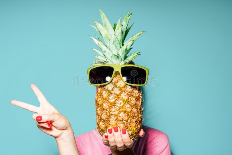 Frau und Ananas auf ihrer Hauptstellung über Farbhintergrund lizenzfreies stockbild