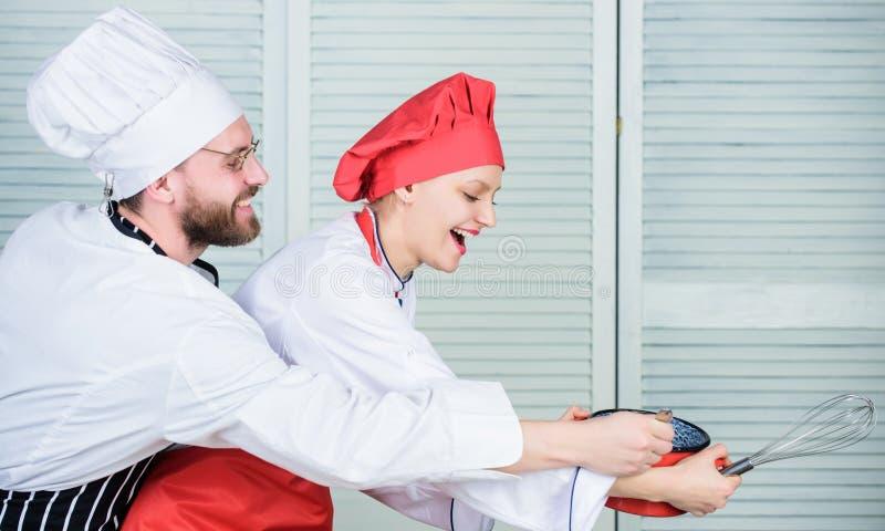Frau und bärtiger Mannchef, die zusammen kochen Kochen der gesunden Mahlzeit K?stliche Mahlzeit Backende Torte zusammen Zusammen  lizenzfreies stockbild