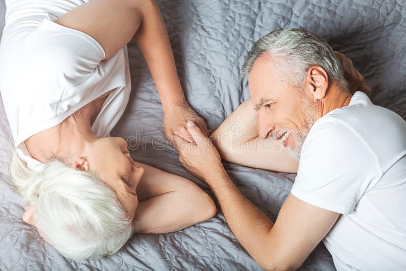 Frau und Ehemann, die auf dem Bett liegen lizenzfreie stockbilder