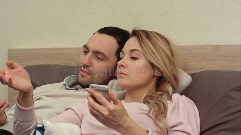 Frau und Ehemann, die den lustigen Film, besprechend, Frau aufpasst, die Smartphone verwendet stockfotografie