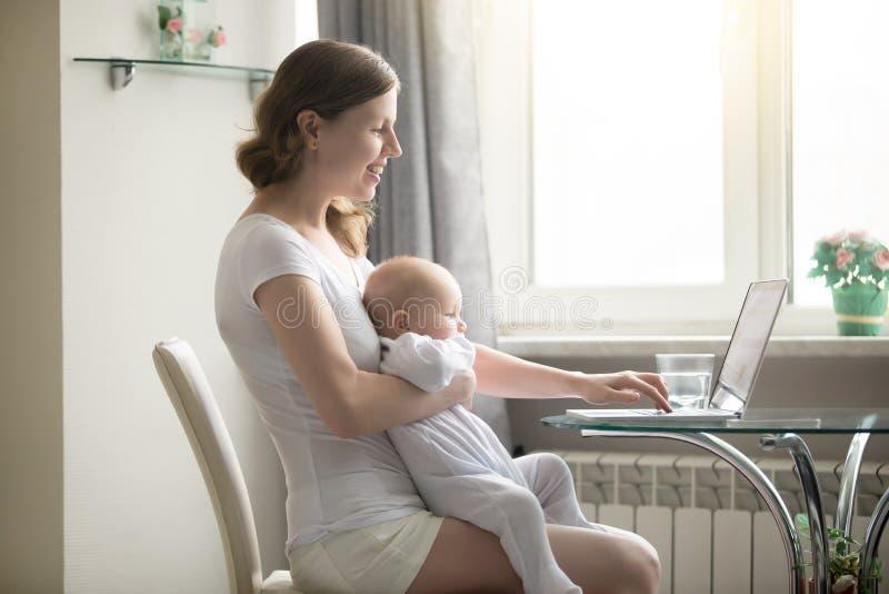 Frau und ein Baby am Laptop stockfotos