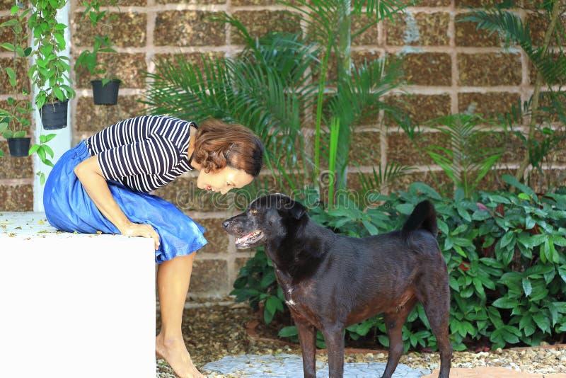 Frau und ein Hund im Garten lizenzfreie stockfotos