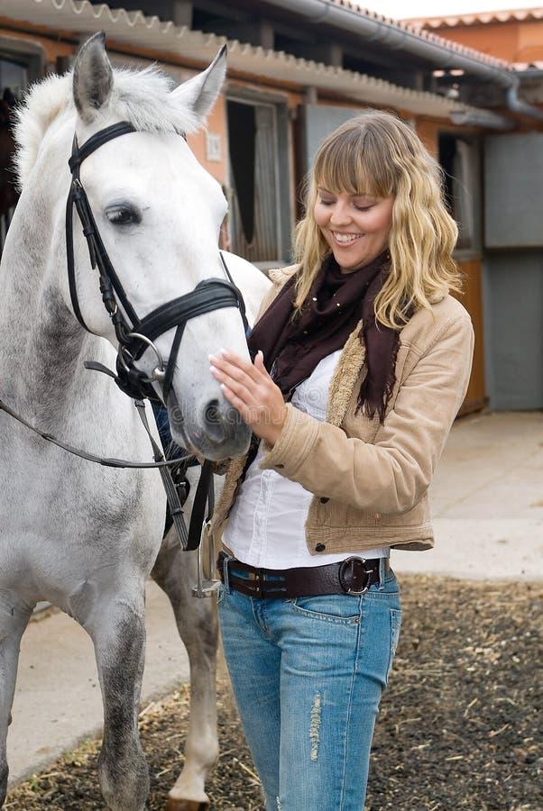 Frau und ein weißes Pferd stockbild
