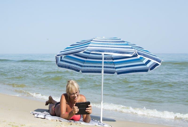 Frau und eine elektronische Tablette stockfotos