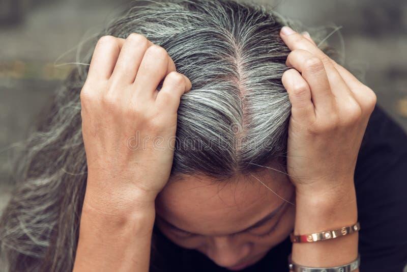 Frau und graues Haar mit dem besorgten betonten Gesicht, das unten schaut lizenzfreie stockfotos