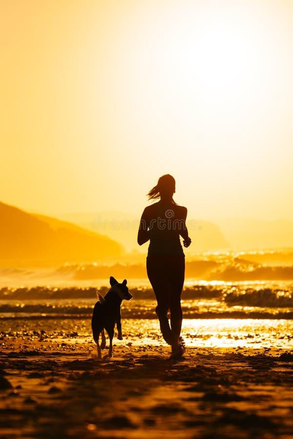 Frau und Hund, die auf Strand bei Sonnenaufgang laufen lizenzfreies stockbild