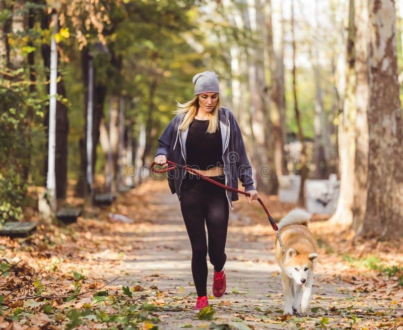 Frau und Hund, die im Park rütteln Gesunder Lebensstil lizenzfreies stockfoto