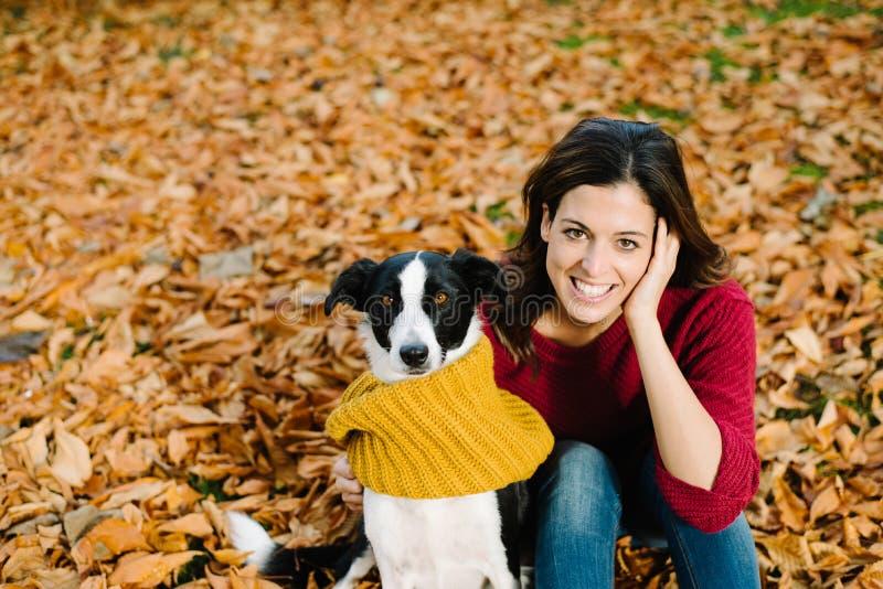 Frau und Hund, die zusammen Herbstsaison genießen lizenzfreies stockfoto