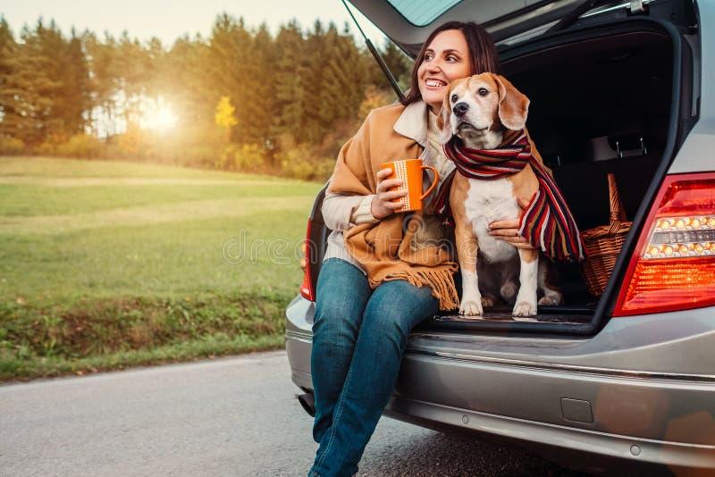 Frau und Hund mit Schalen sitzt zusammen im Autokofferraum auf Herbst stockfotografie