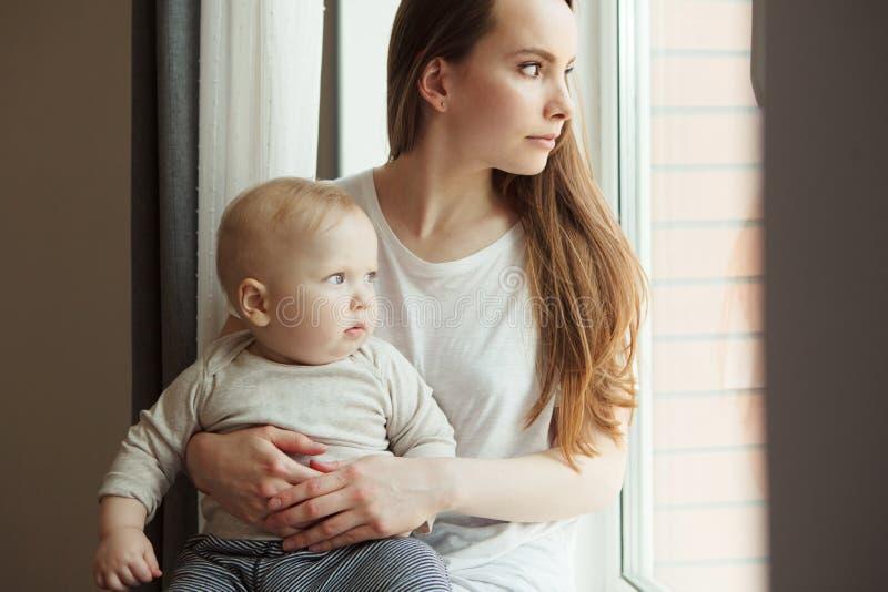 Frau und ihr entzückendes Babykind, die im Fenster schauen stockbild