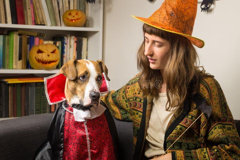 Frau und ihr Hund kleideten oben für Haupt-Halloween-Partei an stockfotografie