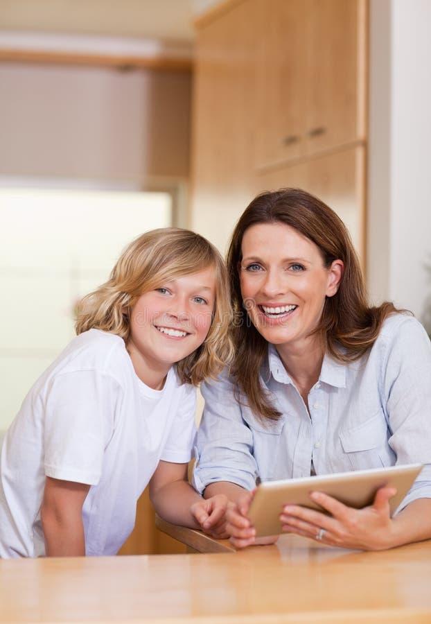 Frau und ihr Sohn, der Tablette in der Küche verwendet stockbild